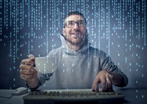 Young man sitting in front of a computer screen with binary code passing on the screen
